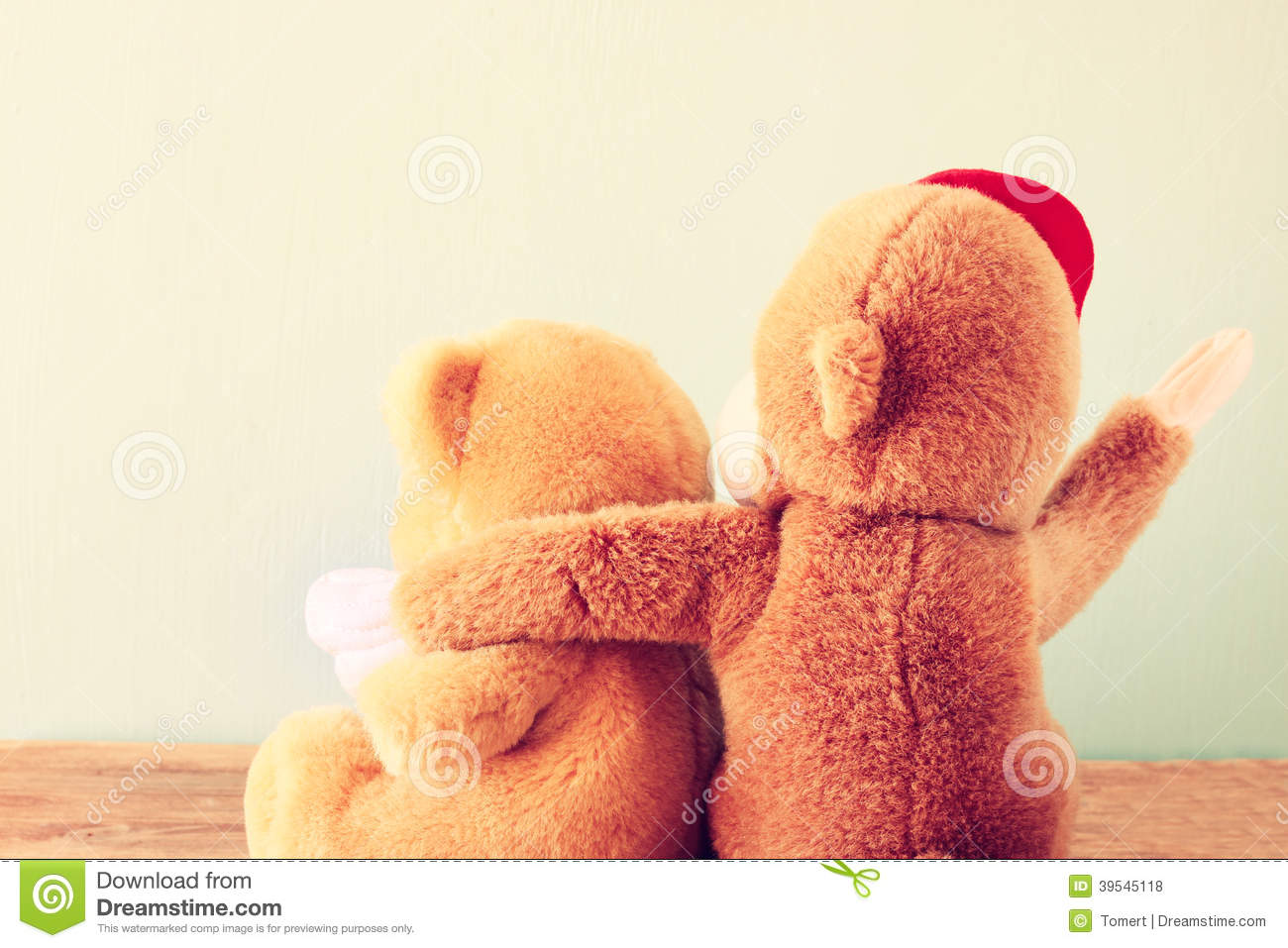 Two teddy bears on a shelf with arms around each other.