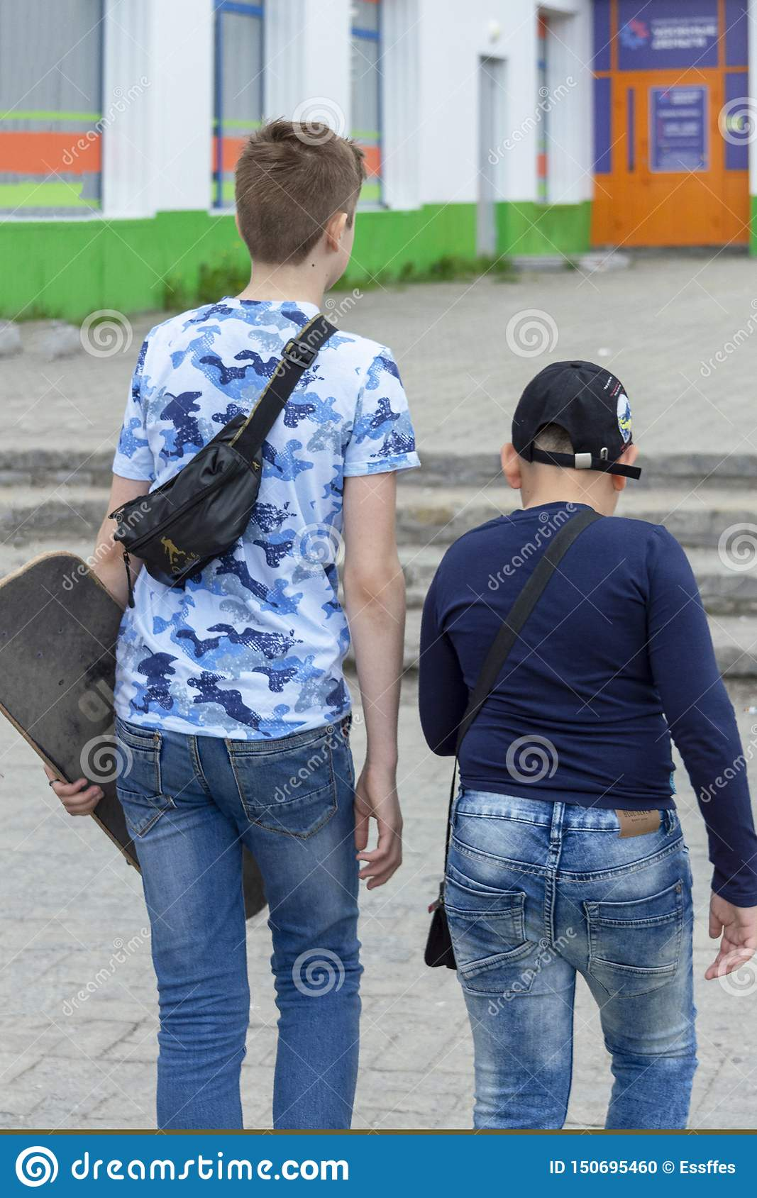 Two teen guys walk down the street in the city