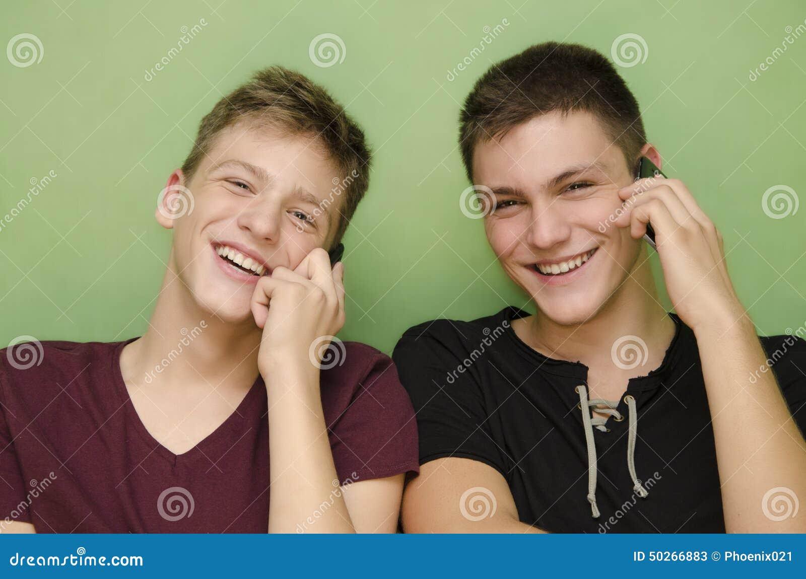 Two teenage brothers talking on smart phone