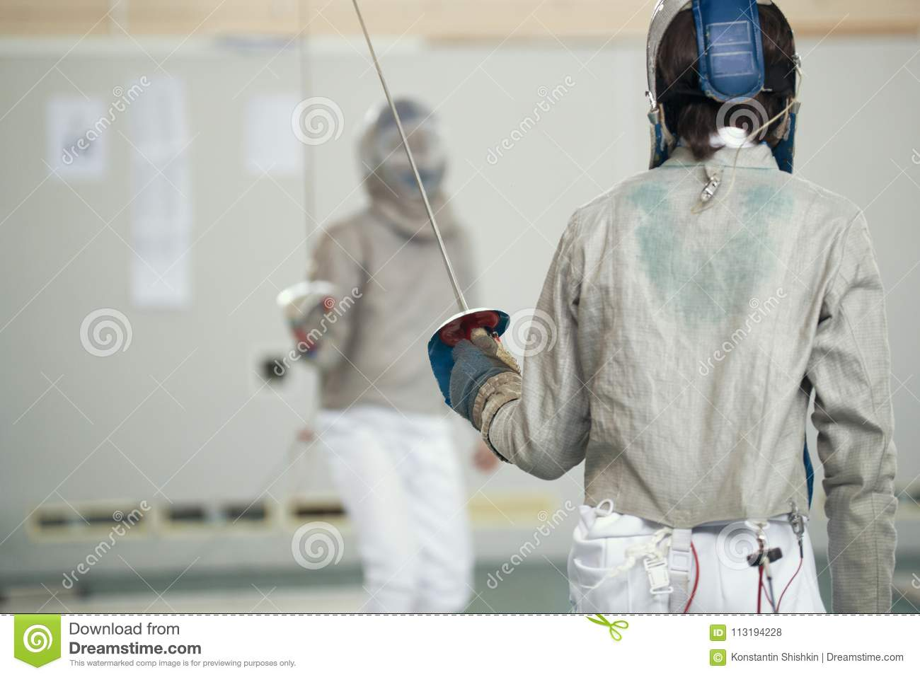 Two teenager fencers in white protective clothes fighting on the fencing tournament