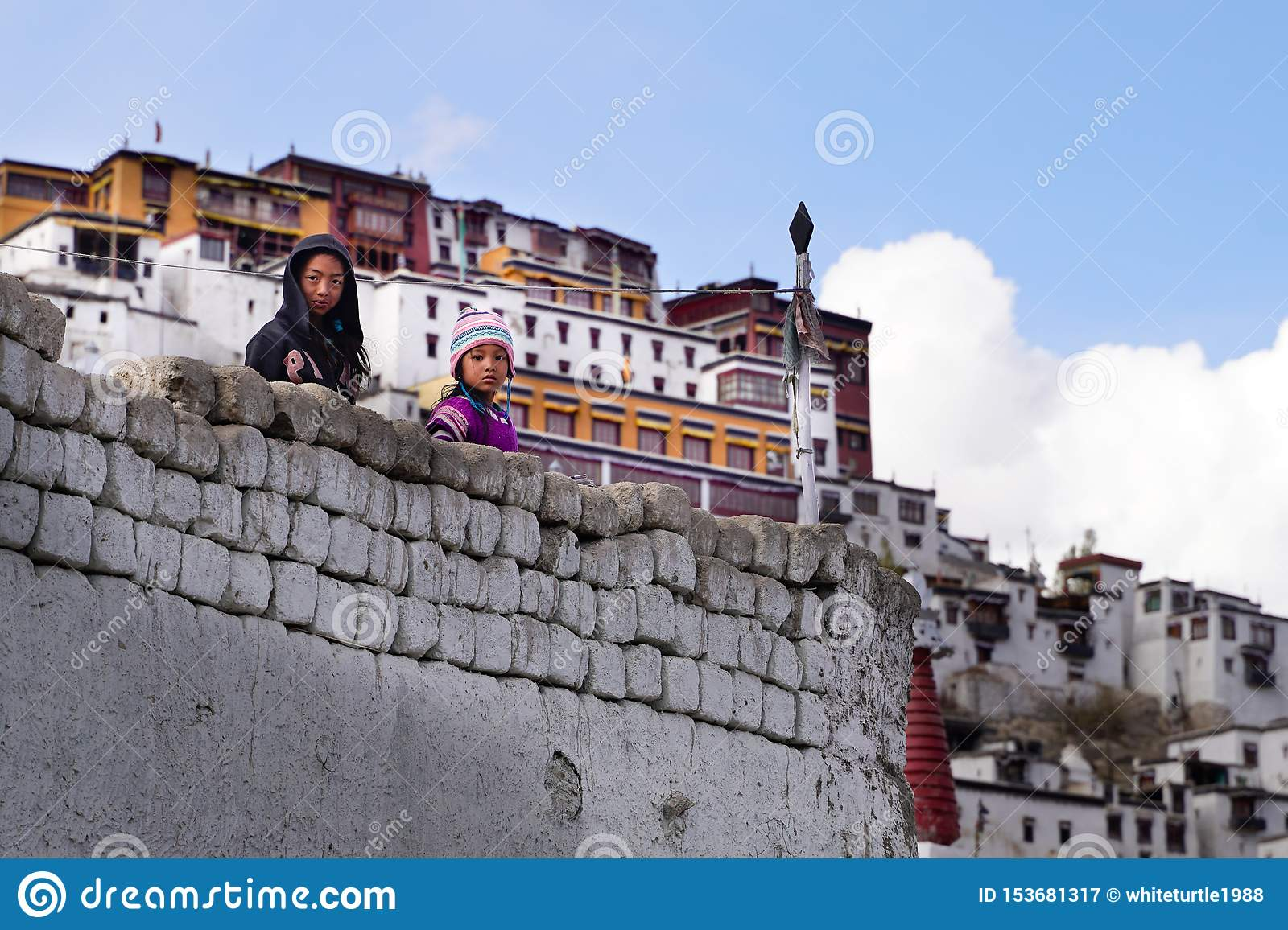 The two tibetan girls staying and looking from the wall