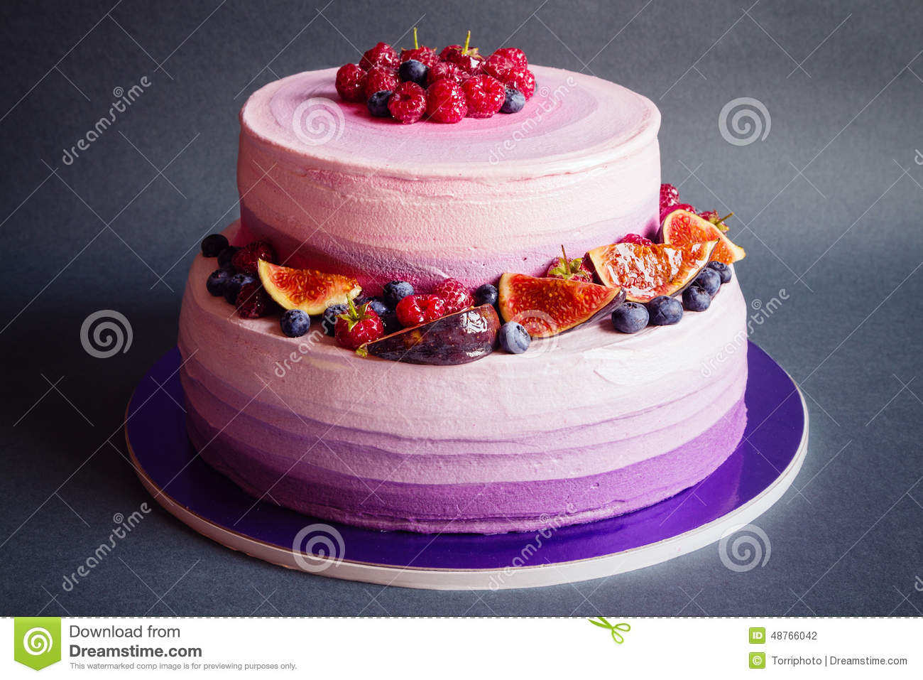 Two Tiered Purple Cake With Fruit On Dark Gray Background