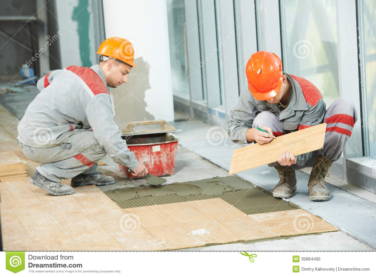 Floor Tile Workers : Two tilers at industrial floor tiling renovation stock