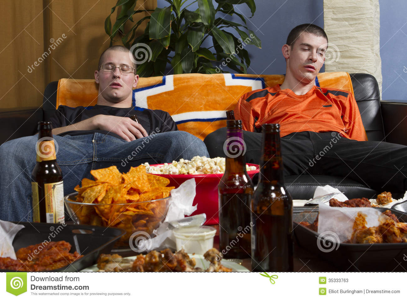 two tired men after watching sports game on tv horizontal stock two tired men after watching sports game on tv horizontal