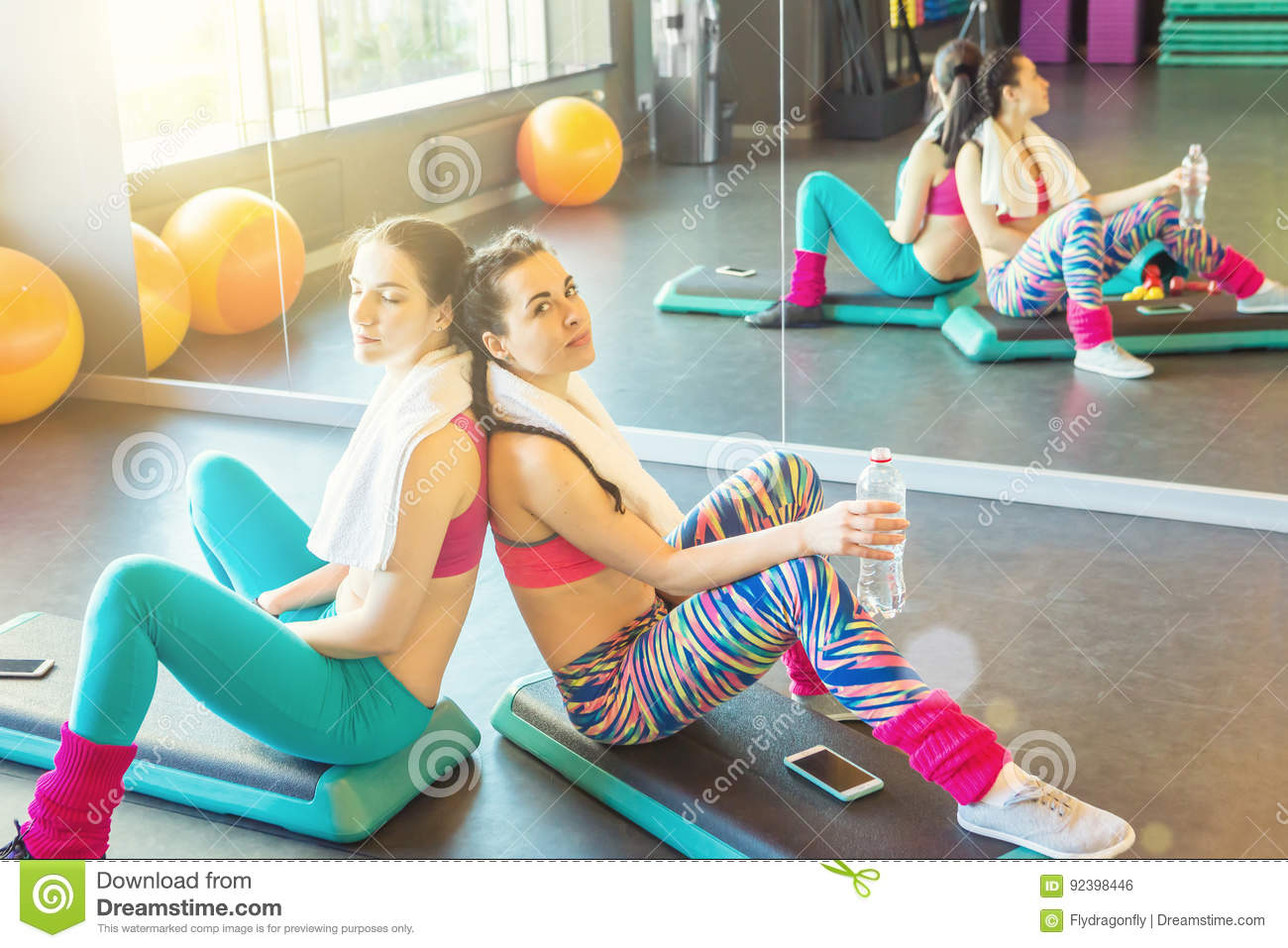 Two tired sports girls resting after active workout.