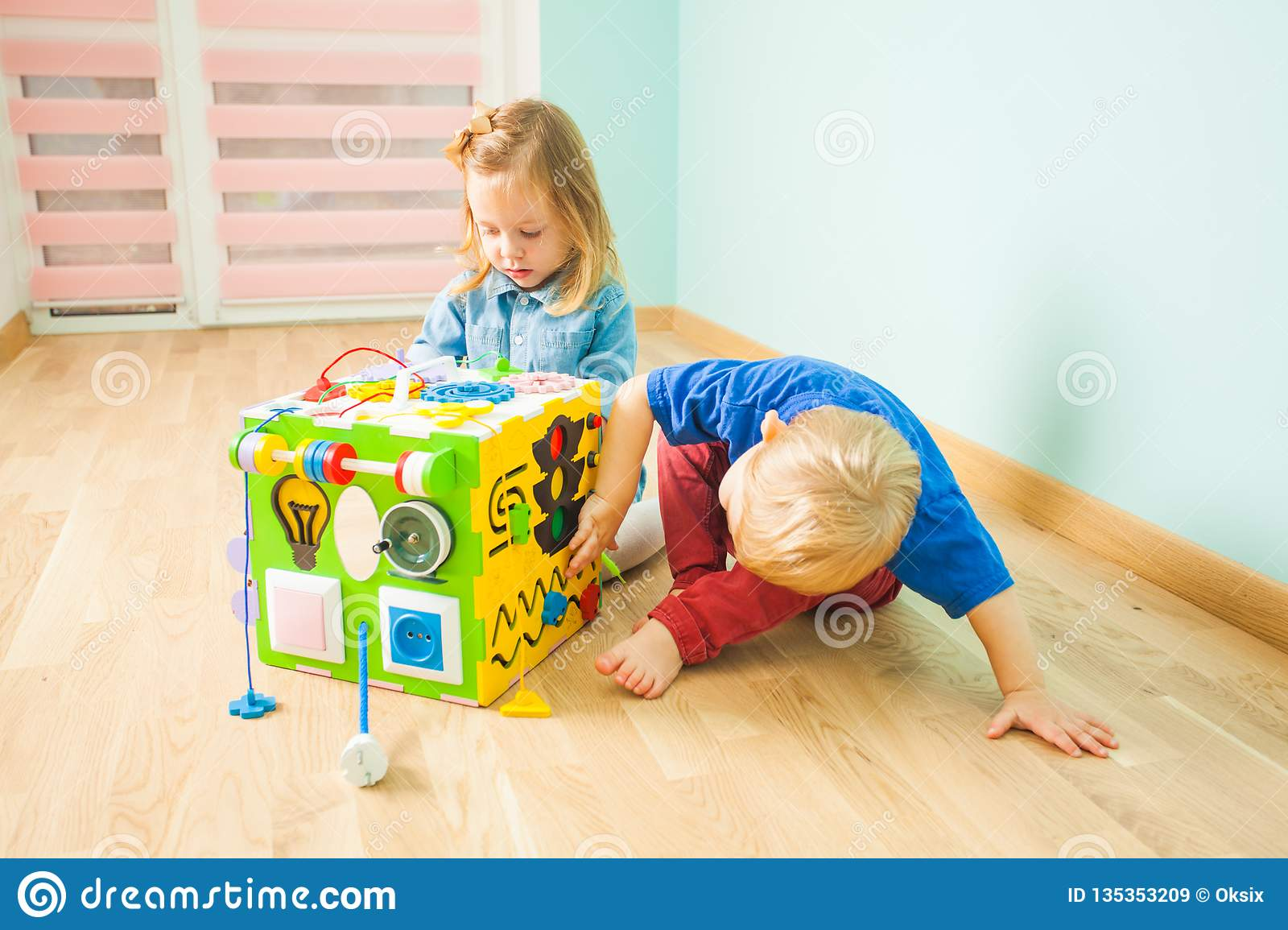 Two Toddlers Sitting On A Floor Near Large Toy Stock Image ...
