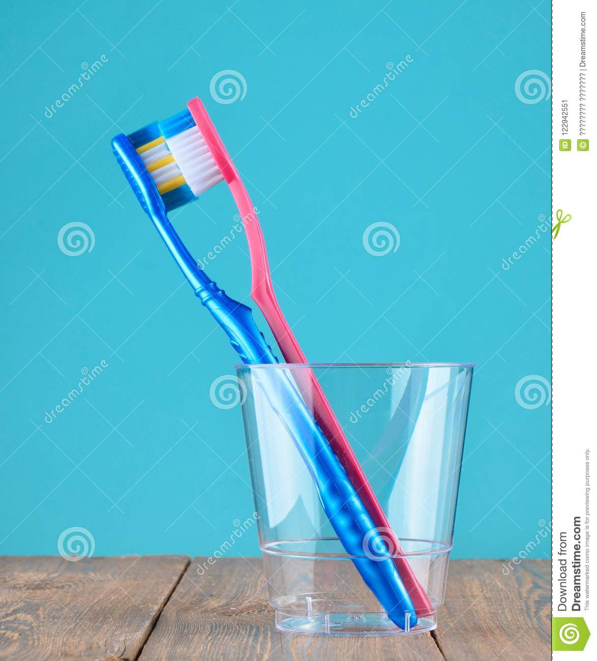 Two toothbrushes in a transparent plastic cup in the bathroom on a blue background, minimalism.