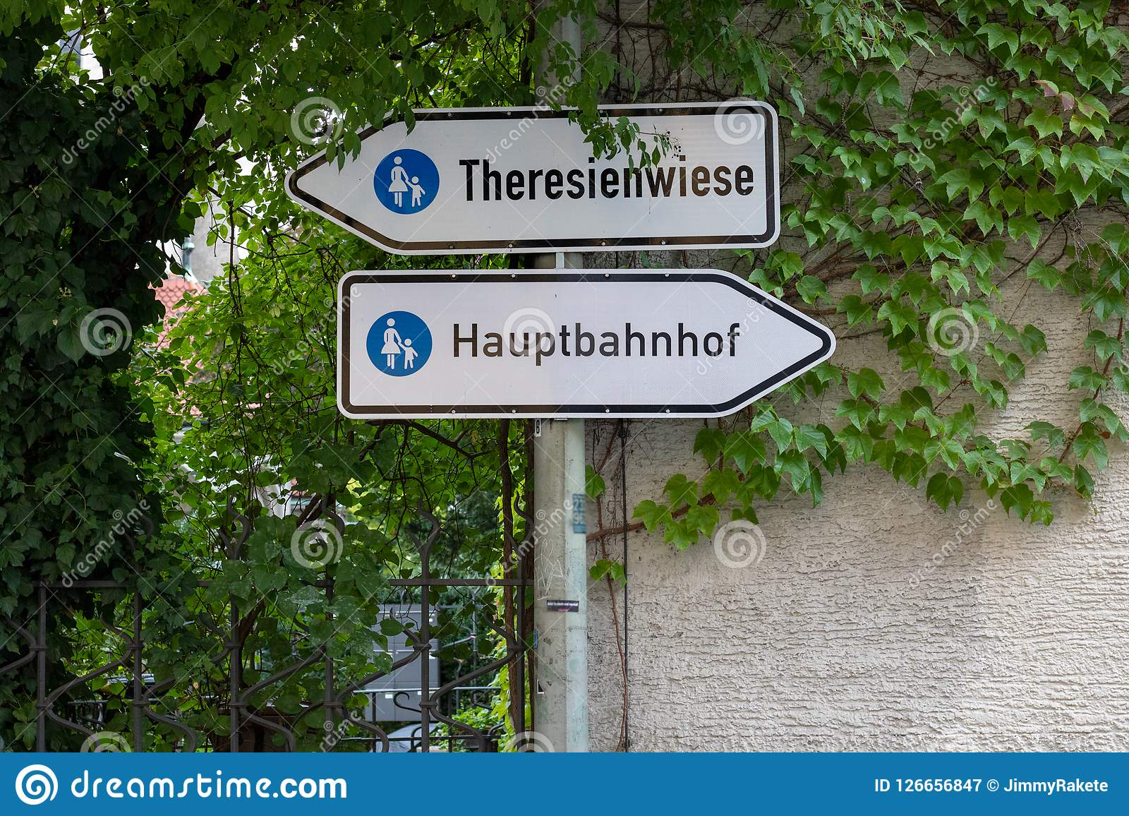 Two traffic signs `Theresienwiese` place of the octoberfest and `Hauptbahnhof` main station on the way between the main statio