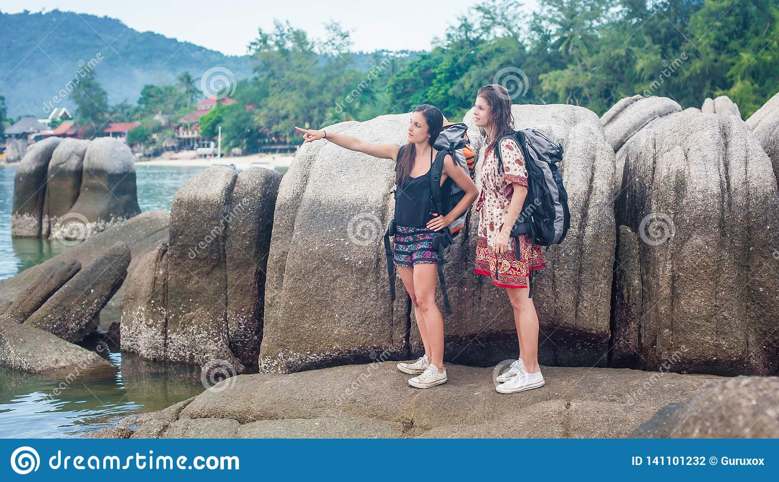 Two traveler woman backpacker relaxing on rock at sunny beach