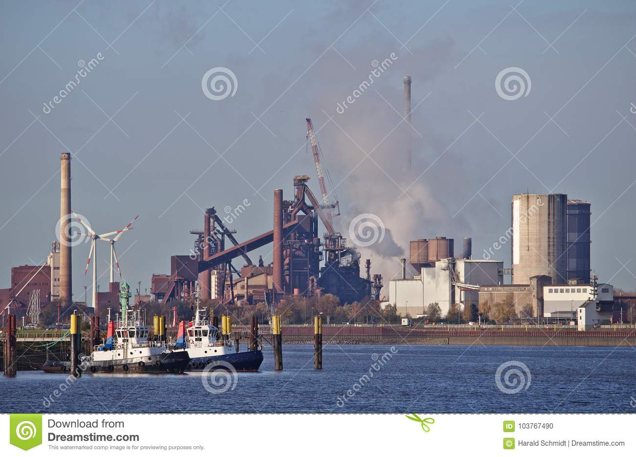 Two tug boats at their moorings with huge steel plant emitting clouds of smoke and wind power stations in the background