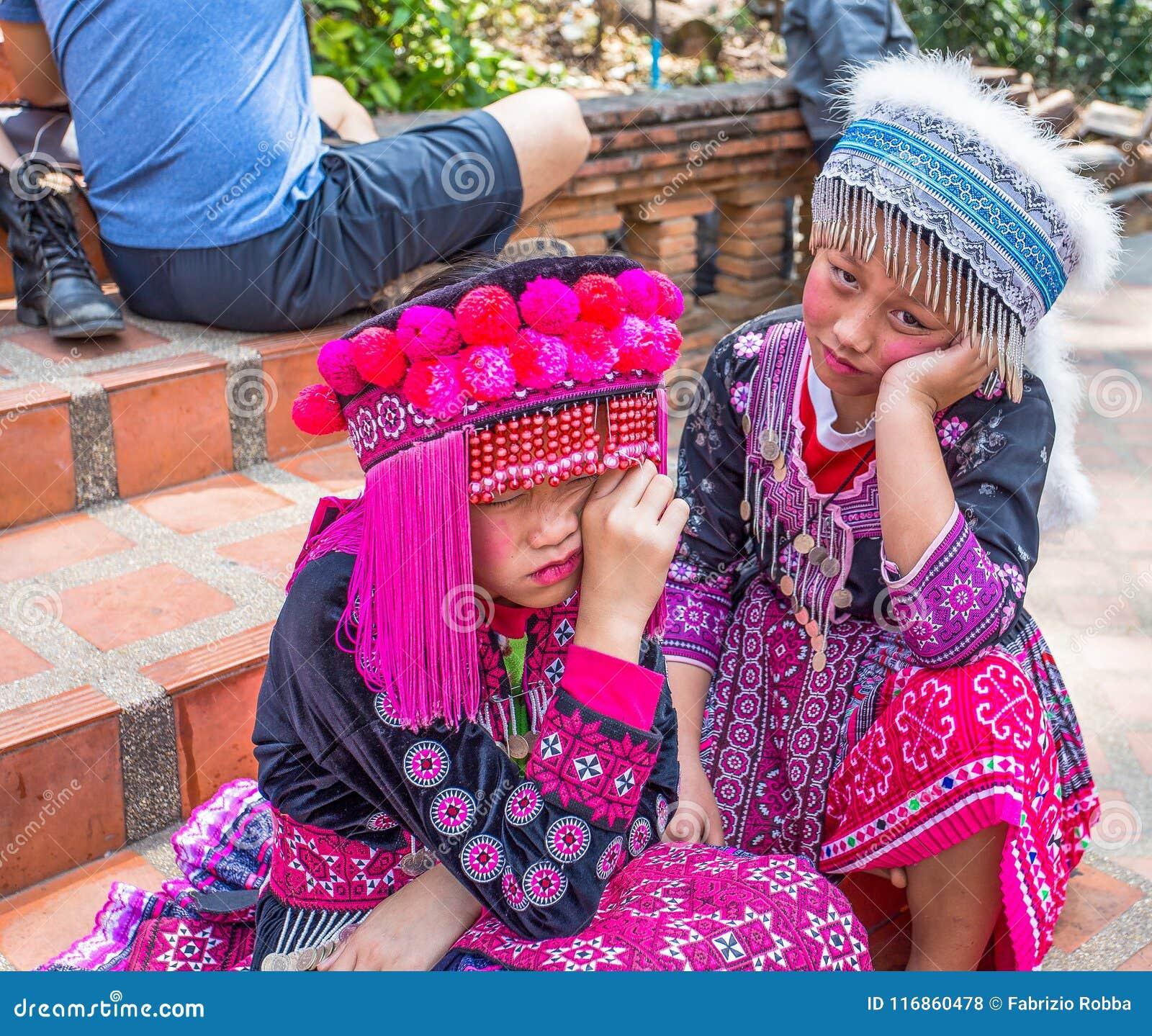Two unidentified Akha children pose for tourist photos at Wat Phratat Doi Suthep on in Chiang Mai, Thailand.