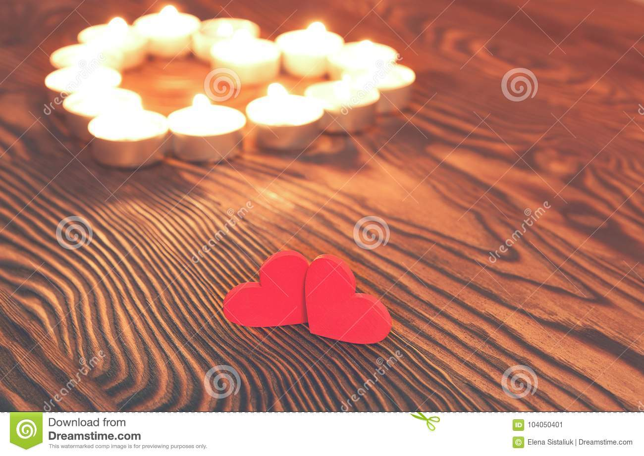 Two hearts, burning candles on wooden. Valentine`s Day.