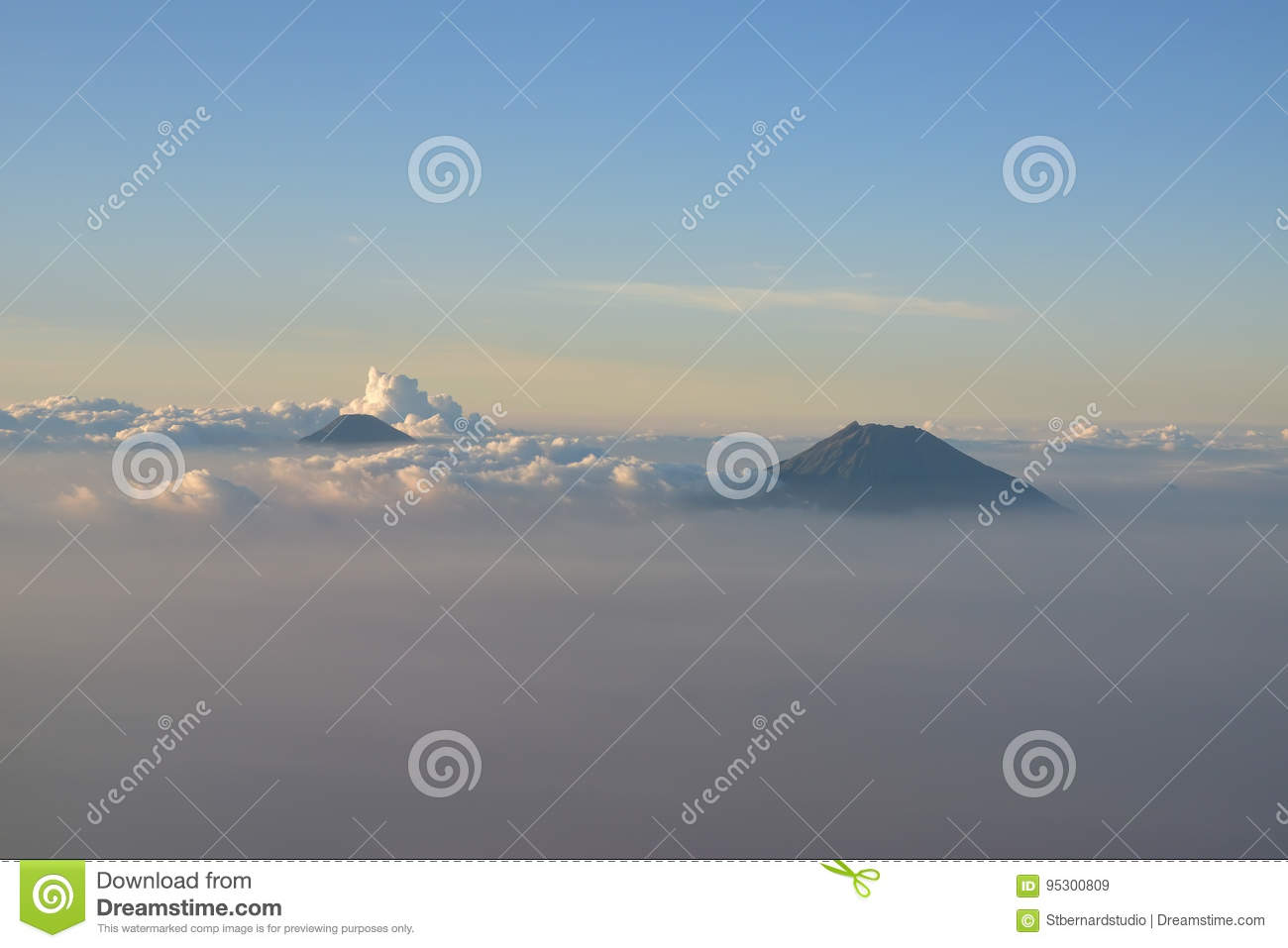 Two volcano mountains visible above the cloud around Yogyakarta, Indonesia near sunset