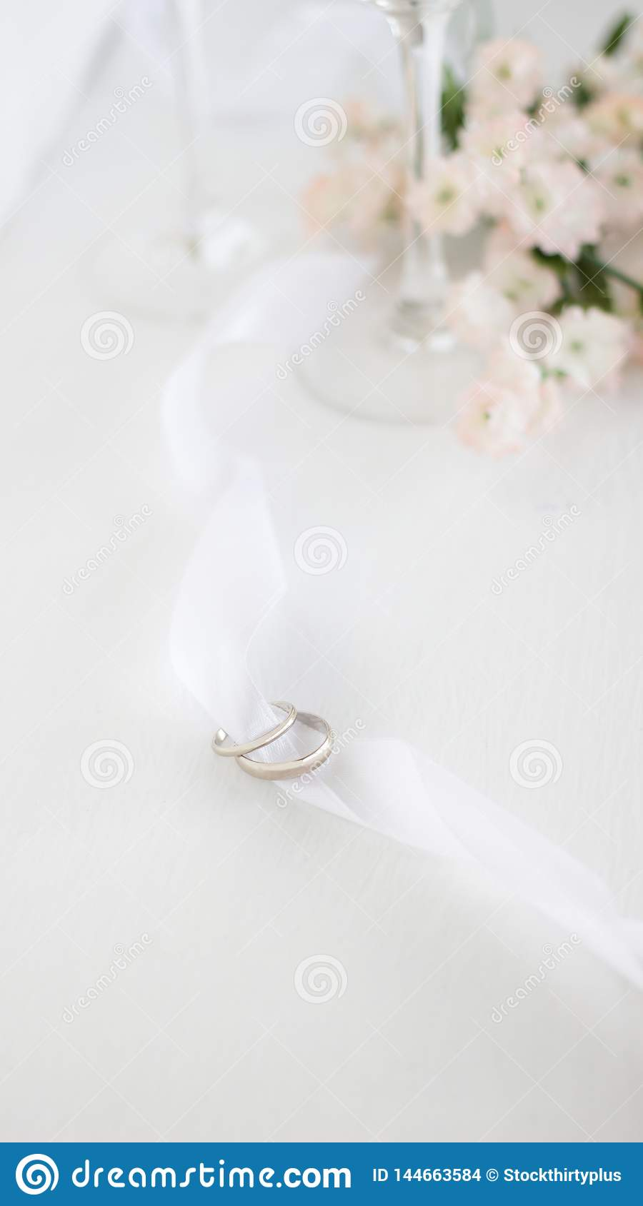 Two wedding rings on white ribbon. Light blur background of flowers and champane glasses .