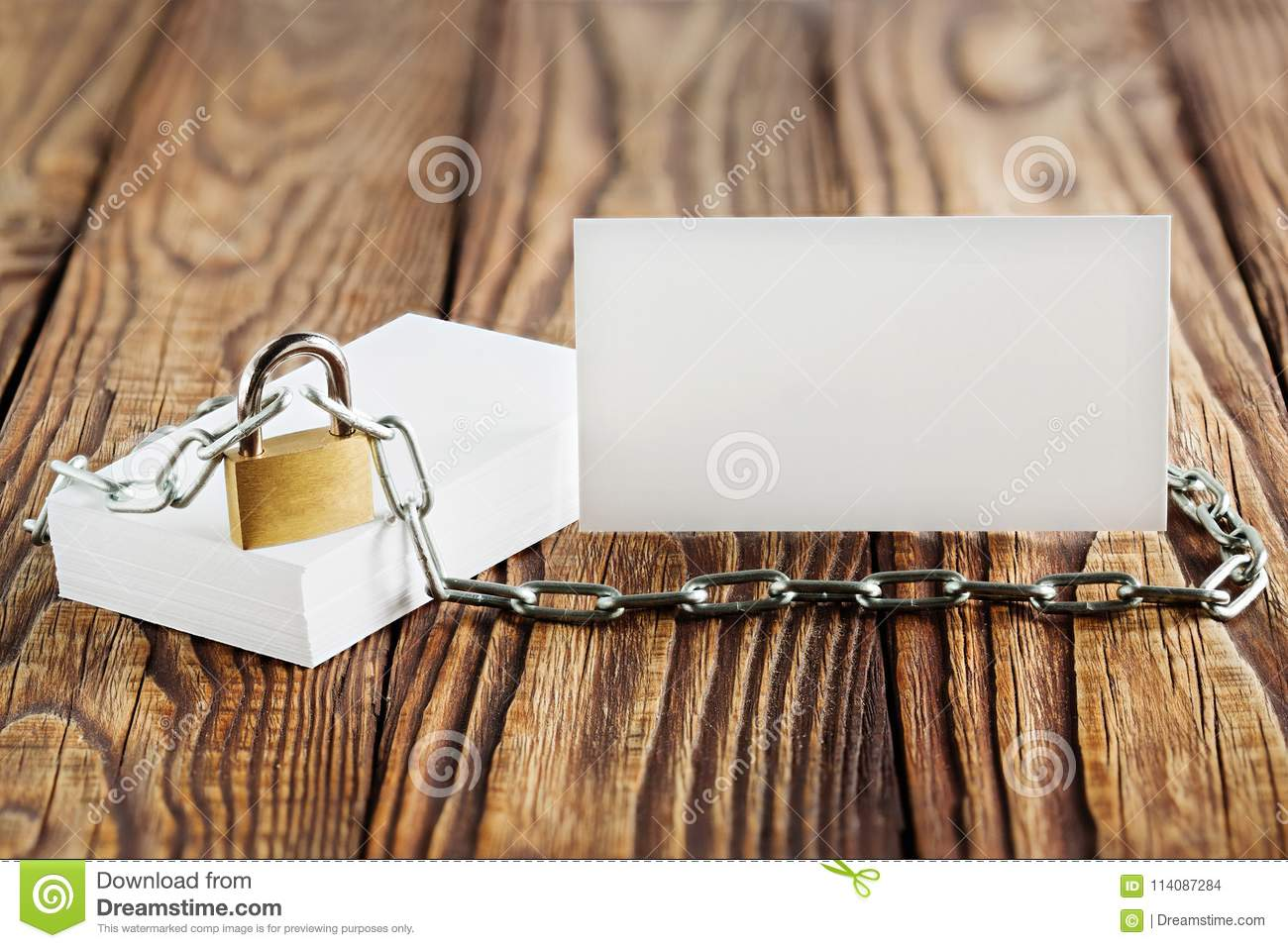 Two white business cards, lock, chain on wooden background . Protection of business and finance. Protection of personal informatio