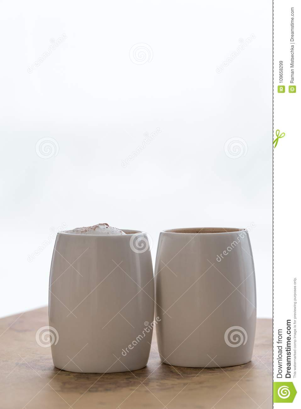 2898df82ac6 Two white cups of coffee stand on a world map against a light background.