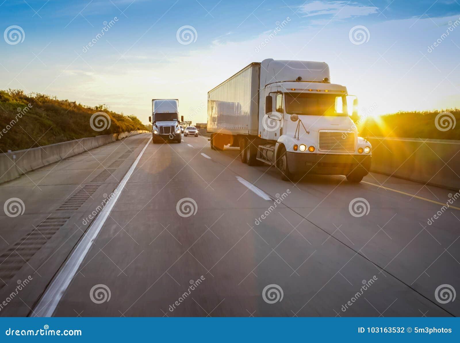 Two white semi trucks on road