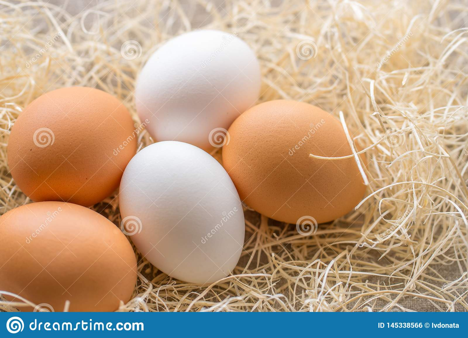 Two white and three brown eggs on the background of hay