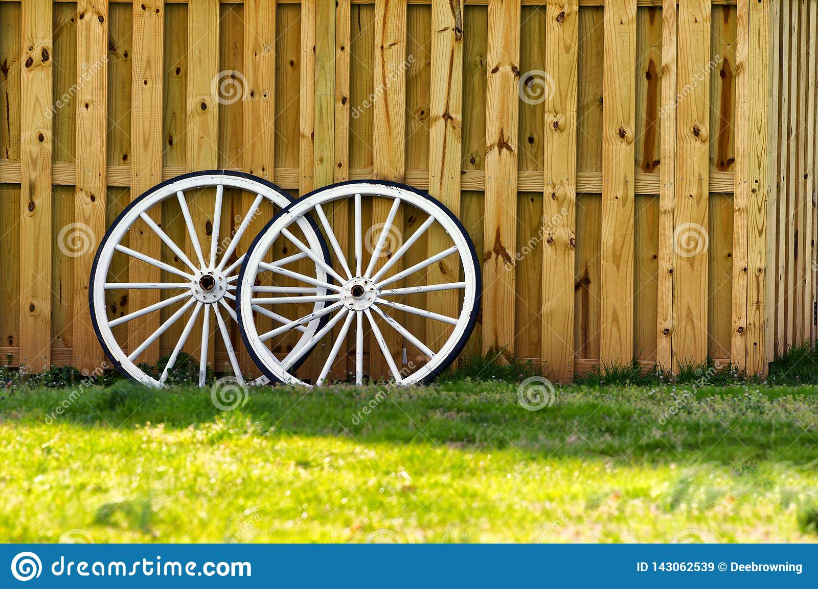 Two White Wagon Wheels Against A Wooden Fence Stock Image Image Of Copy Leaning 143062539