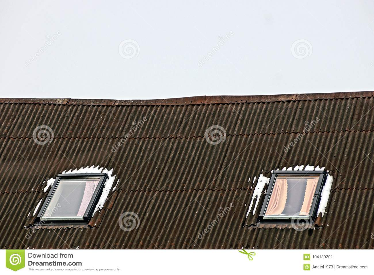 Two windows in the snow on a slate roof against the sky