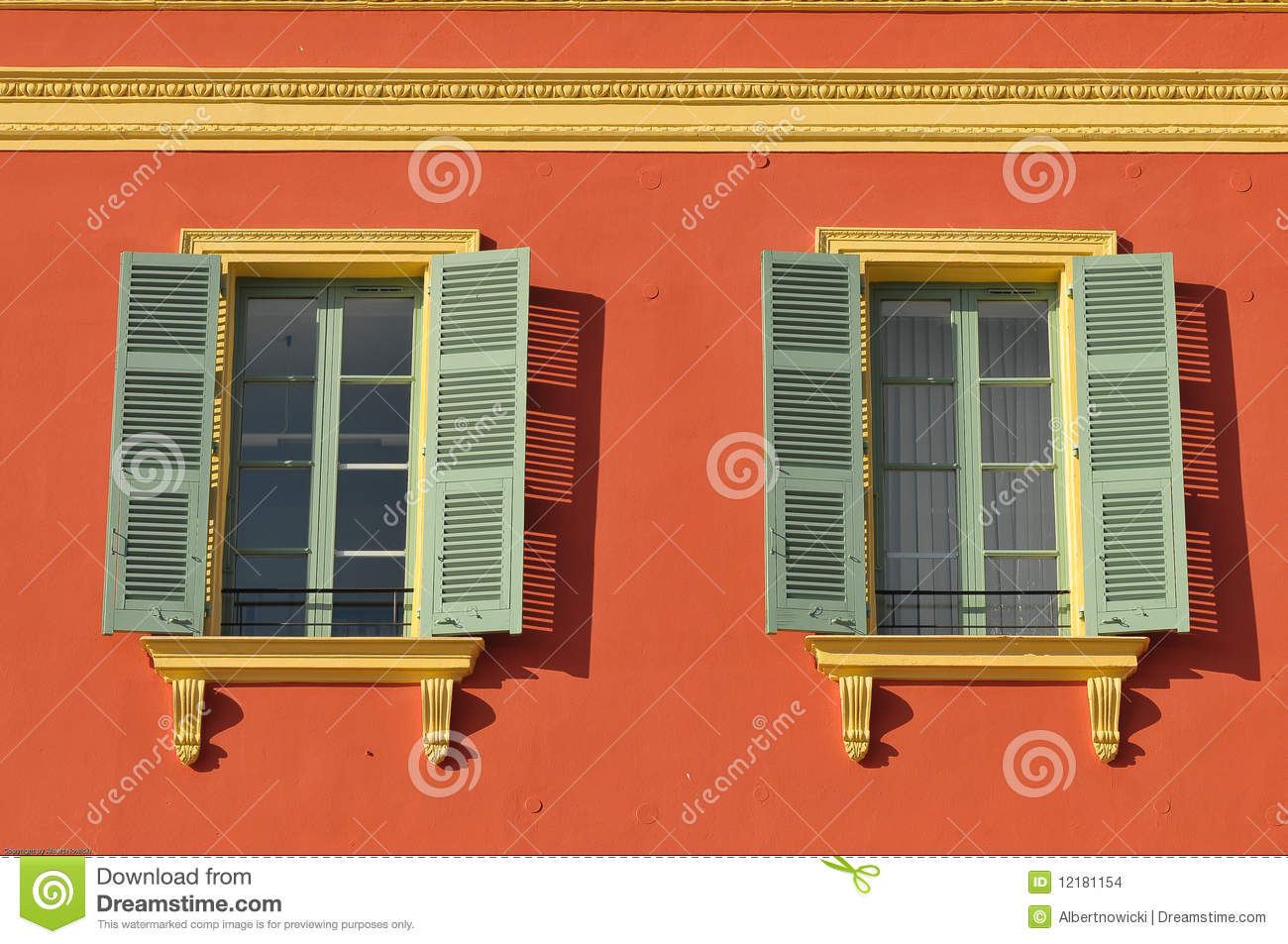 Two Windows With Window Shades Open On A Red Wall Stock