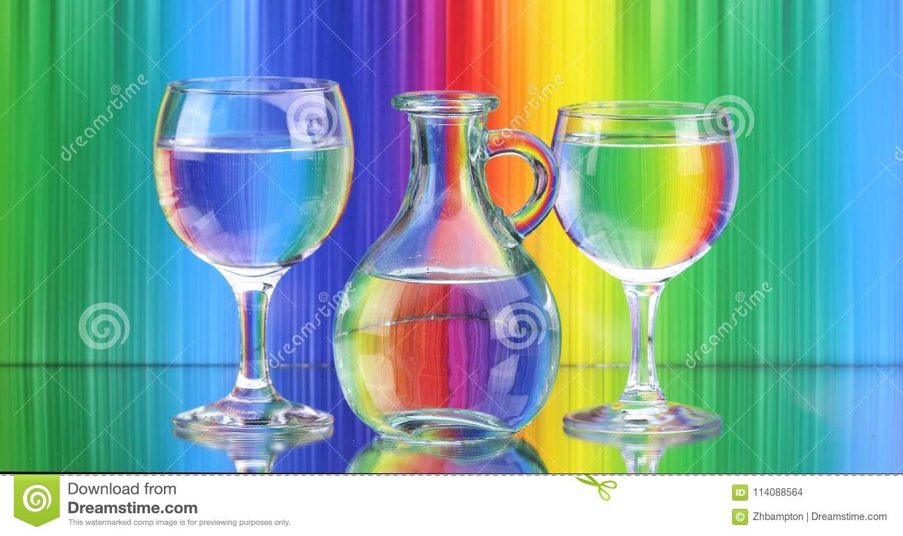 Two wine glasses and a jug of fresh clean water on a coloured background