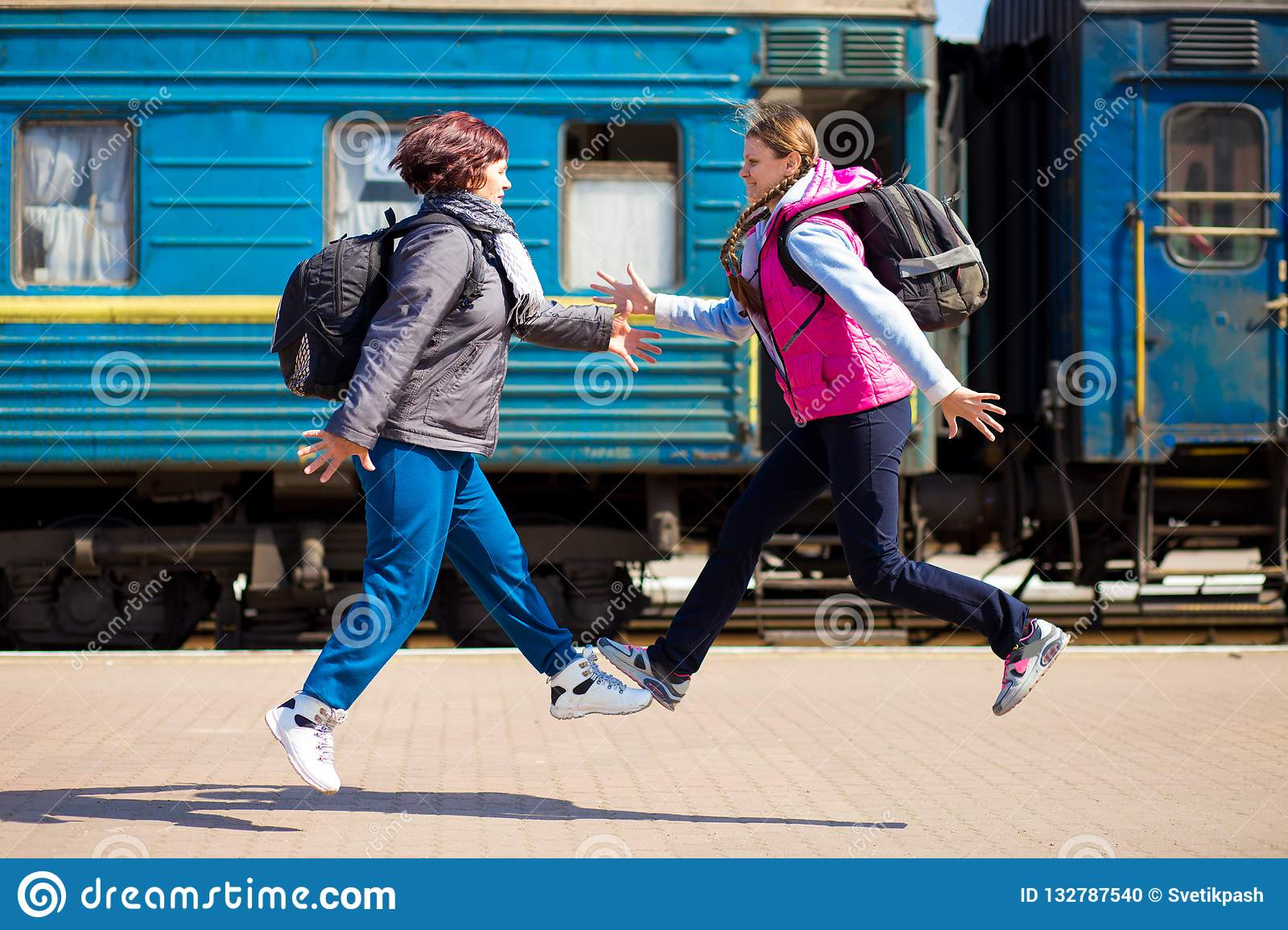 Two woman with backpack run at railway station