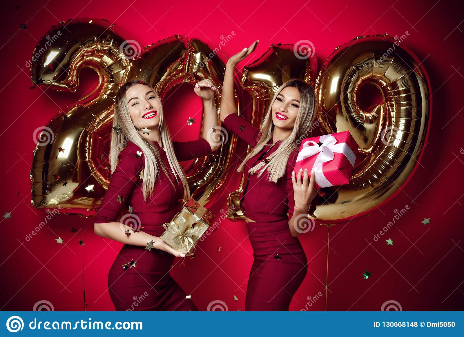 Two women celebrating at new year party happy laughing girls in casual dresses throw gold stars confetti with 2019 balloons