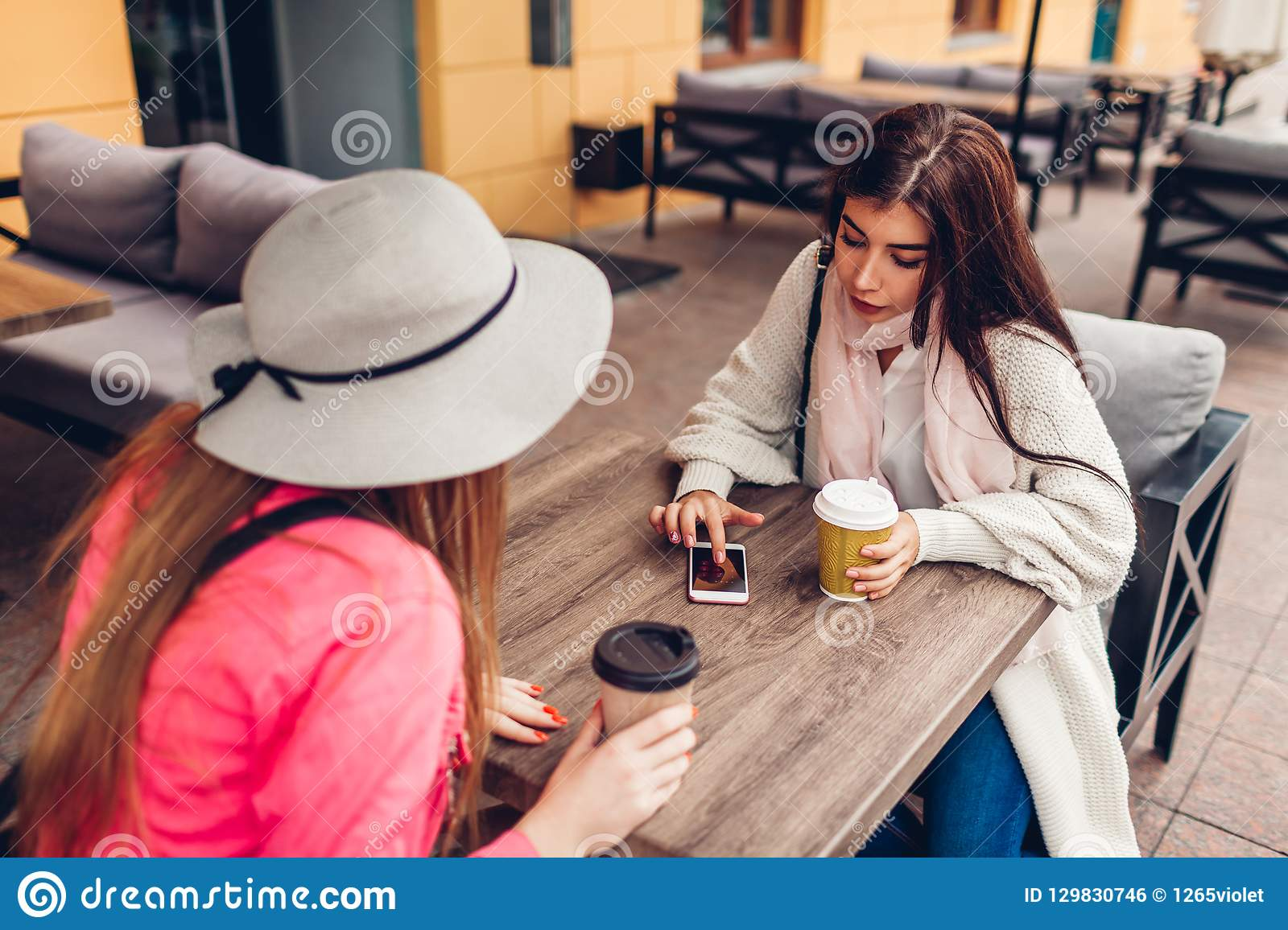Two women chatting while having coffe in outdoor cafe. Happy friends using phone checking pictures. Girls hang out