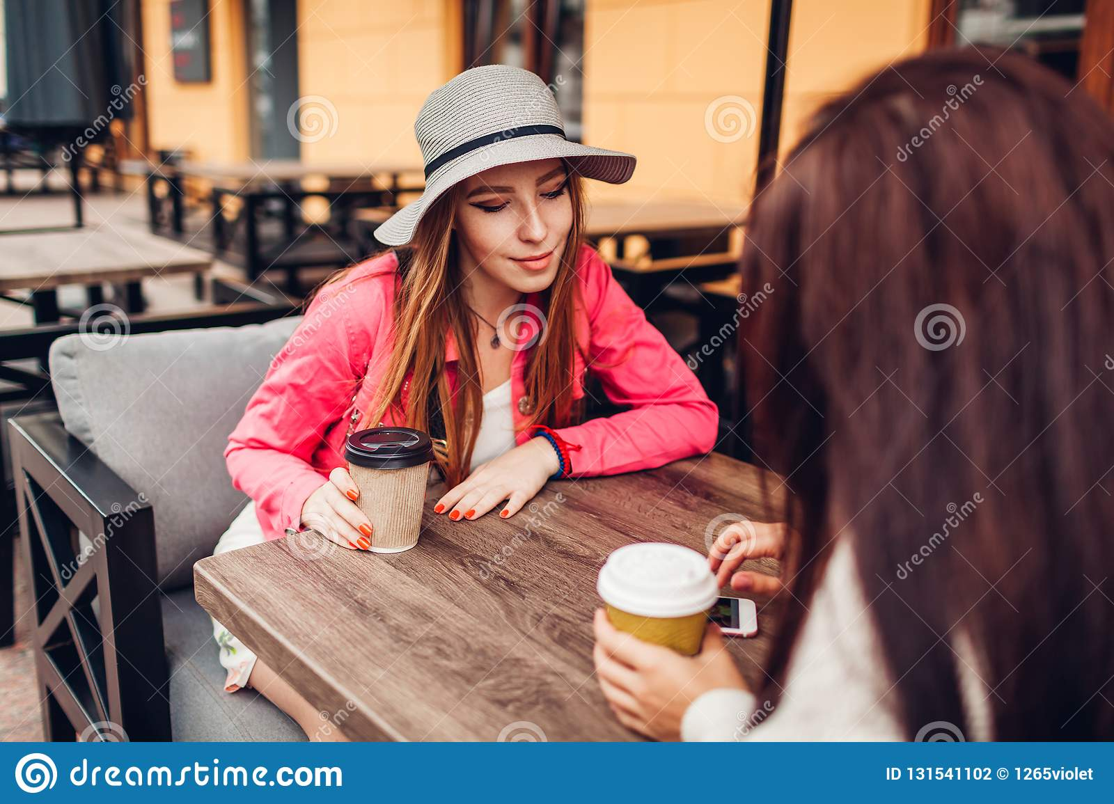 Two women chatting while having coffe in outdoor cafe. Happy friends using phone checking pictures. Girls hang out and having fun
