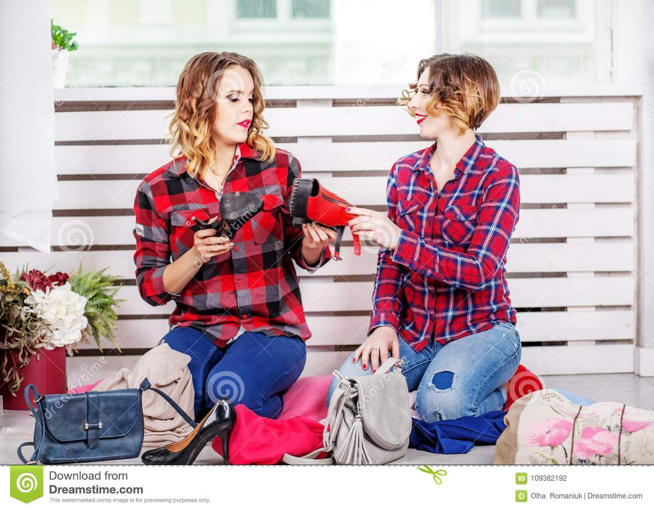 Two women choosing shoes of her wardrobe. The concept of fashion