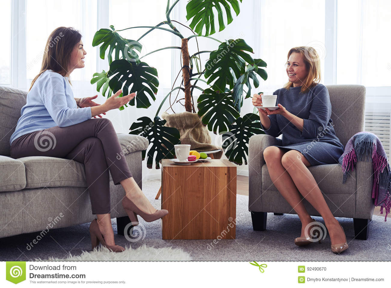 Two women communicating while drinking coffee in living room