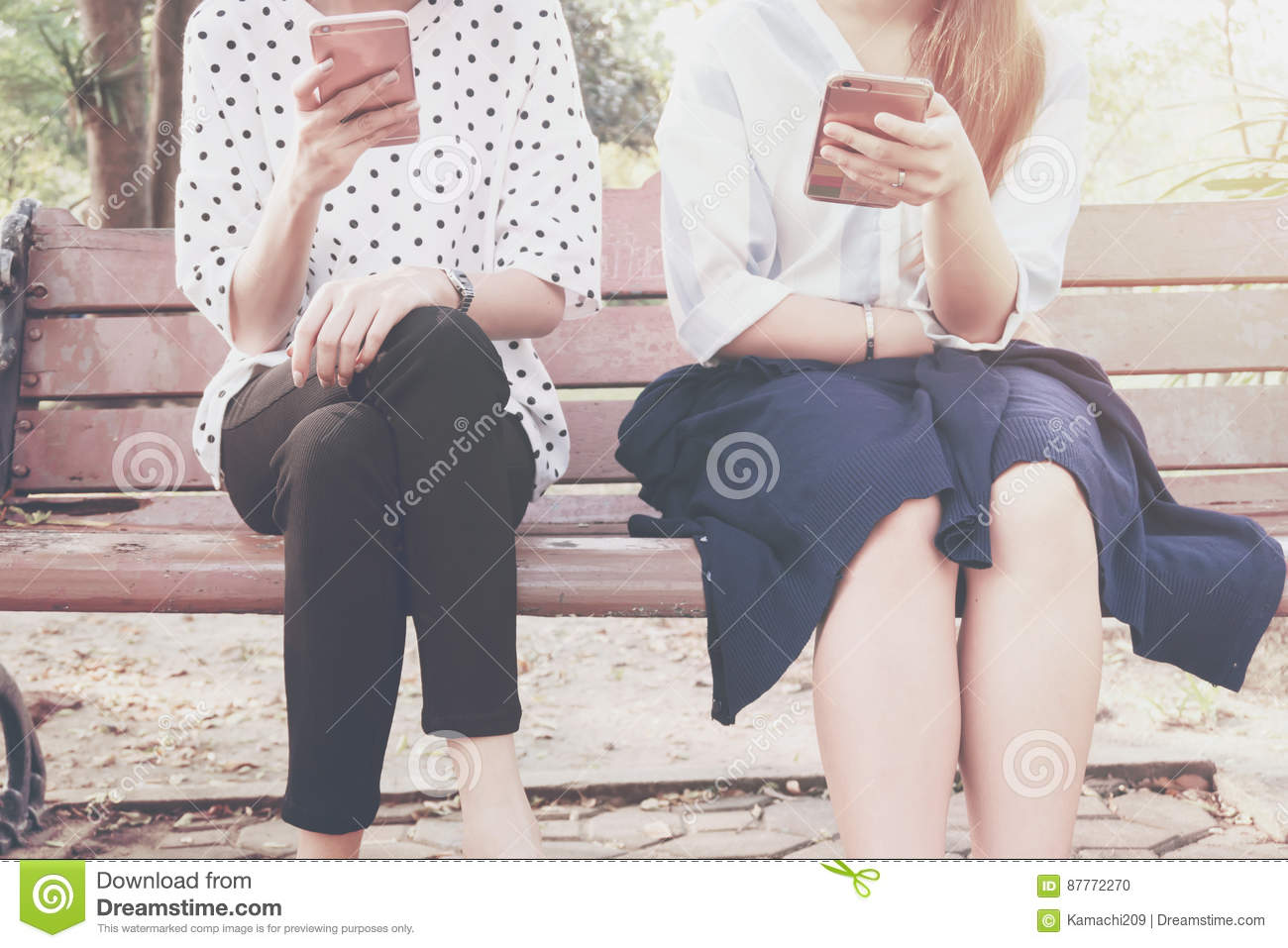 Two women in disinterest moment with smart phones in the outdoor, concept of relationship apathy and using new technology and smar
