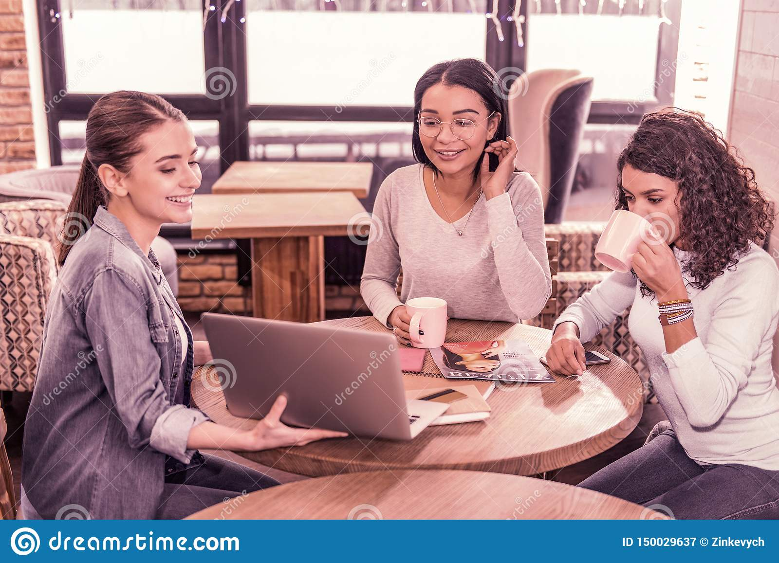Two women drinking tea while watching presentation of their colleague on laptop