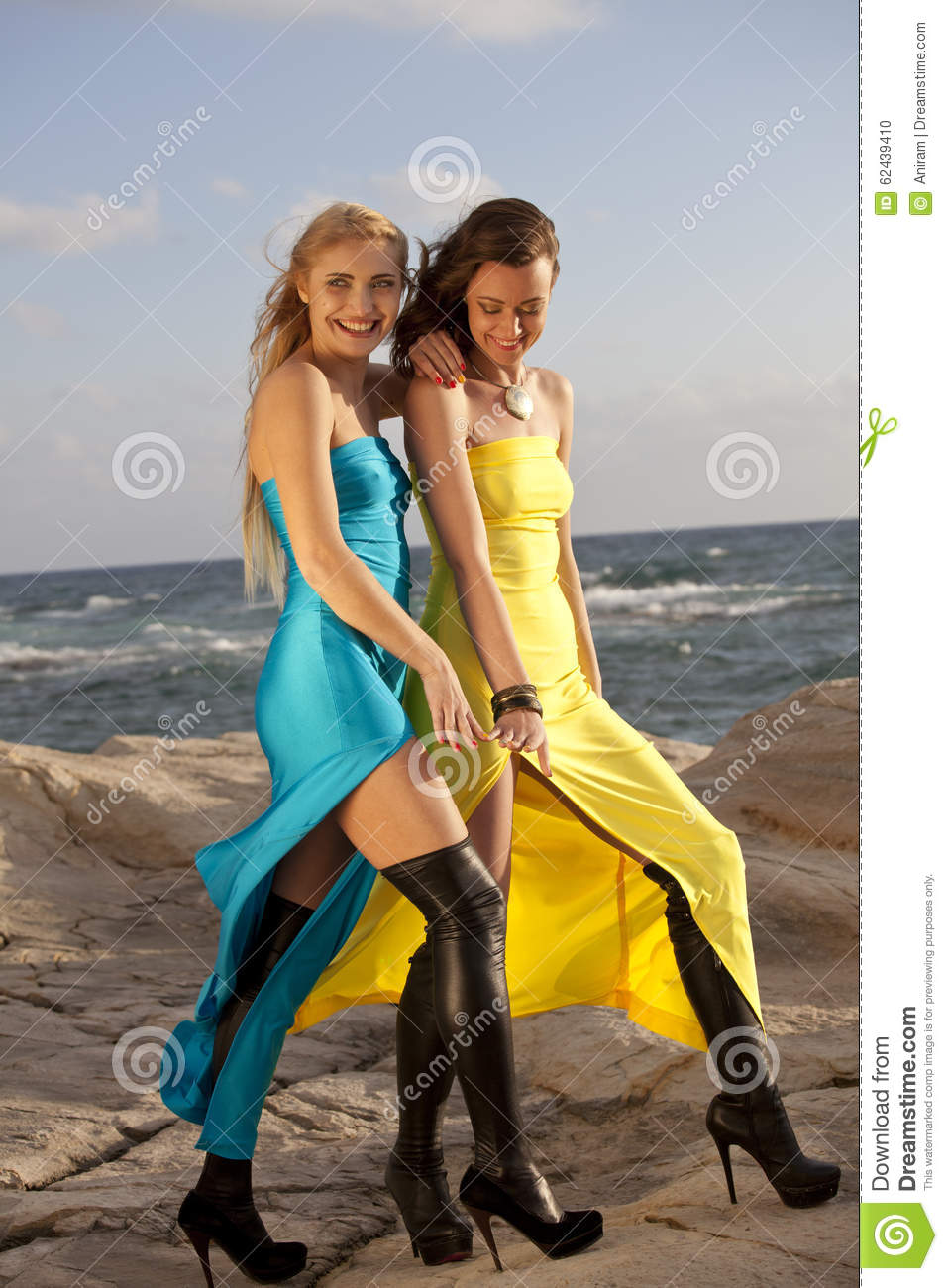 Two women in evening dresses on the beach