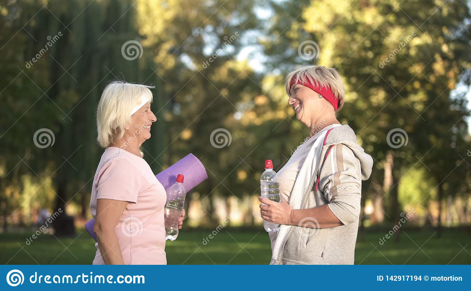 Two women friends meeting before workout in park and giving advices each other