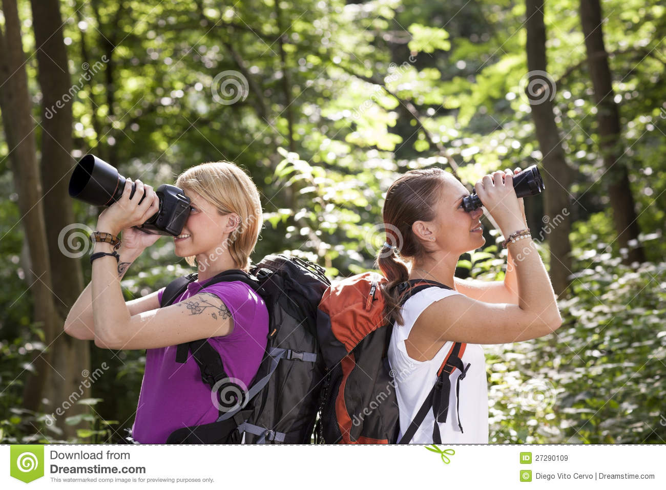 Two women hiking and looking with binoculars