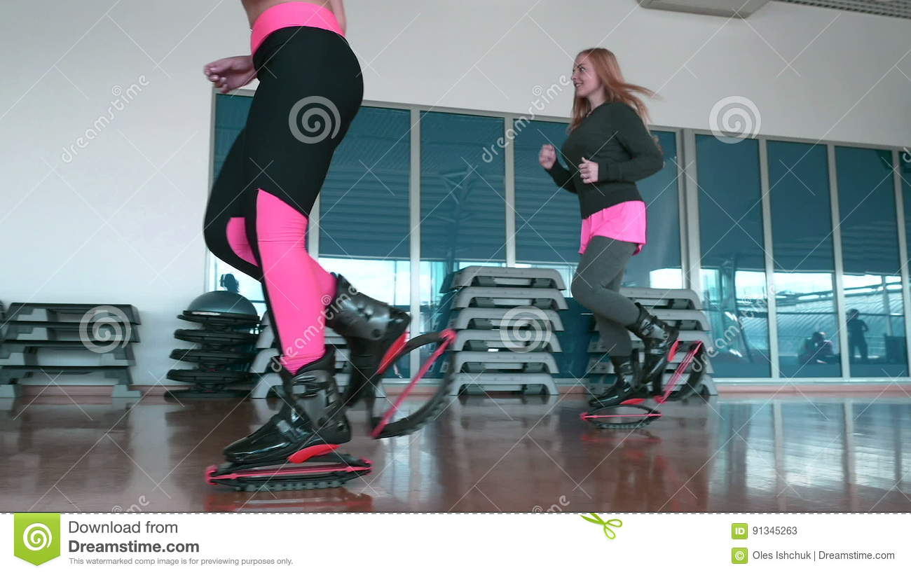 Two Women Jumping In Kangoo Shoes In The Gym Stock Video - Video of