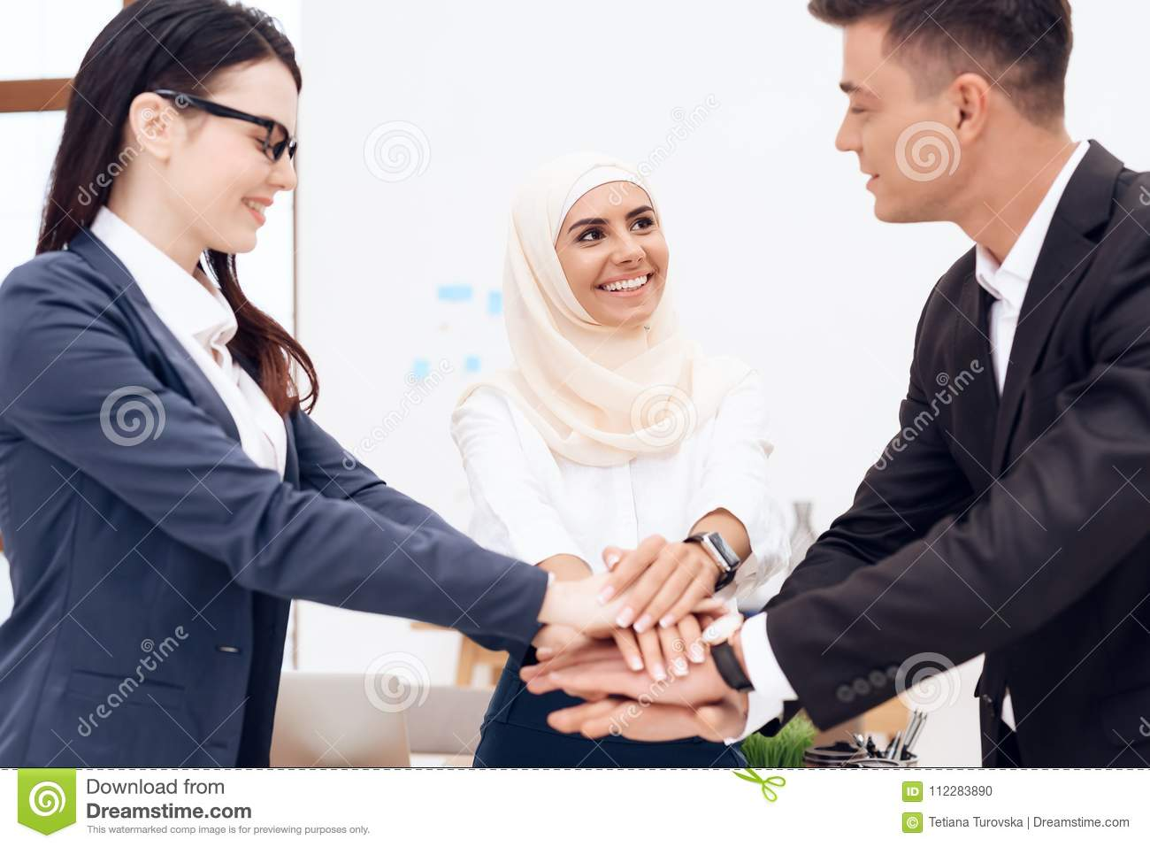 Two Women And A Man Are Holding Each Others Hands Stock Photo
