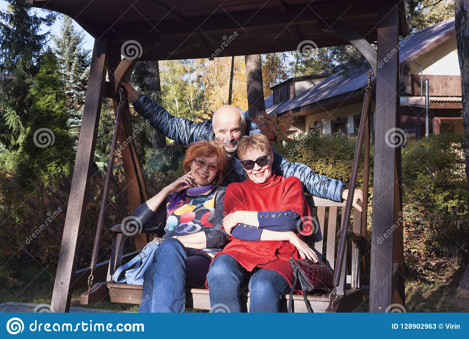 Two Women Of Mature Age On A Bench And Behind Them A Man Stock Image