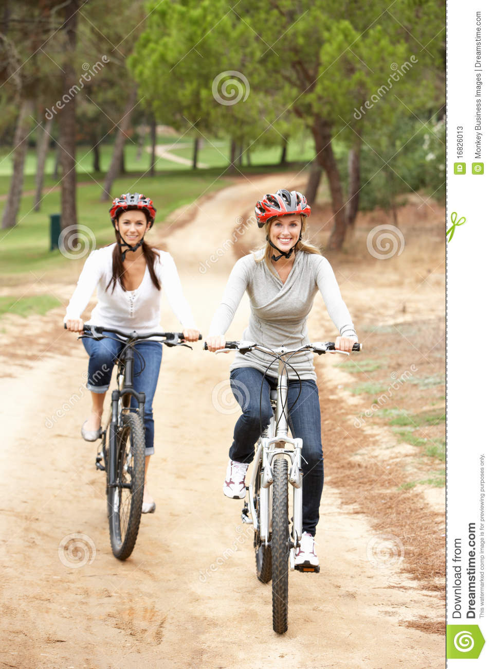 two women riding bicycle in park stock photos image