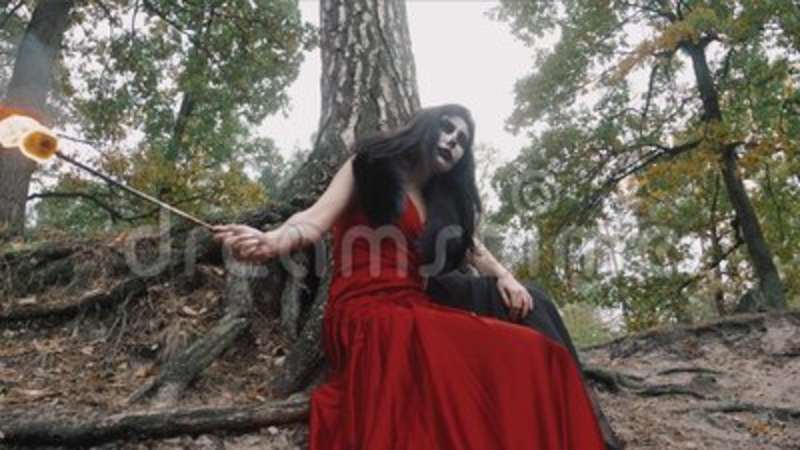 Two women with scary halloween make up in red and black dress sitting near  tree in the forest park outdoors holding fire