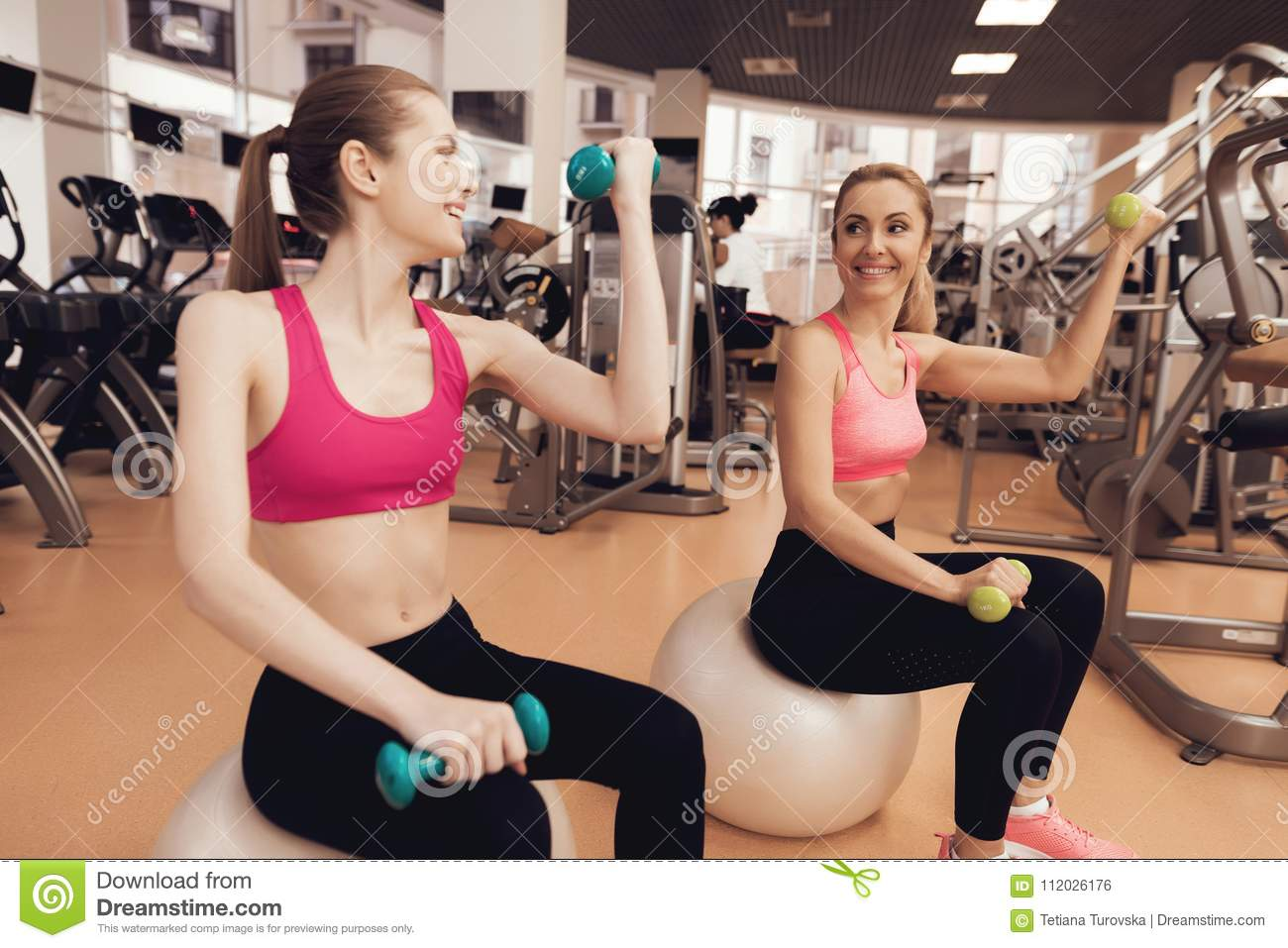 Two women sitting doing exercises with dumbbells at the gym. They look happy, fashionable and fit.