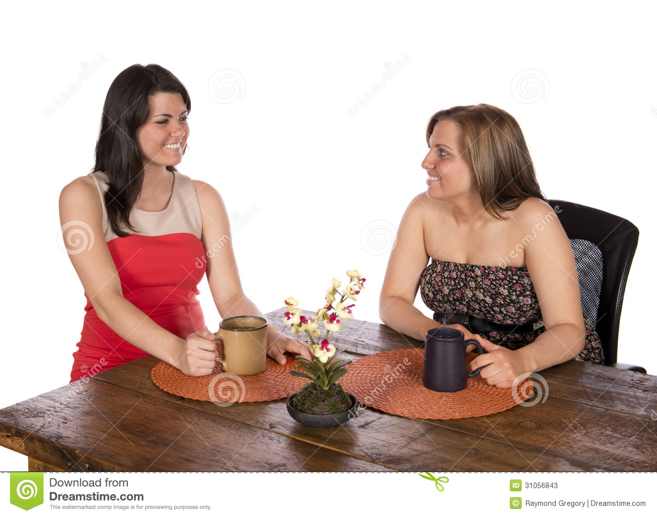 Two Women Sitting Having Coffee At Table Stock Image