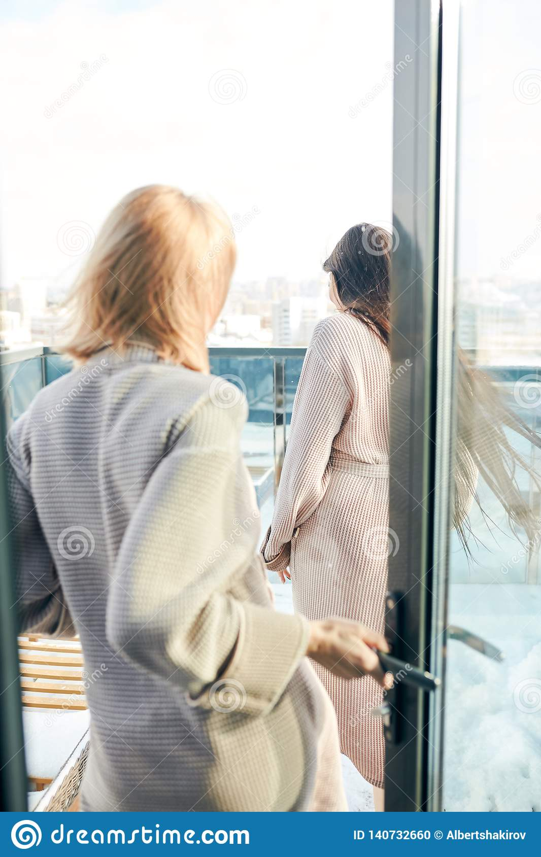 Two women standing in bathrobe on outdoor terrace with winter snowy cityscape