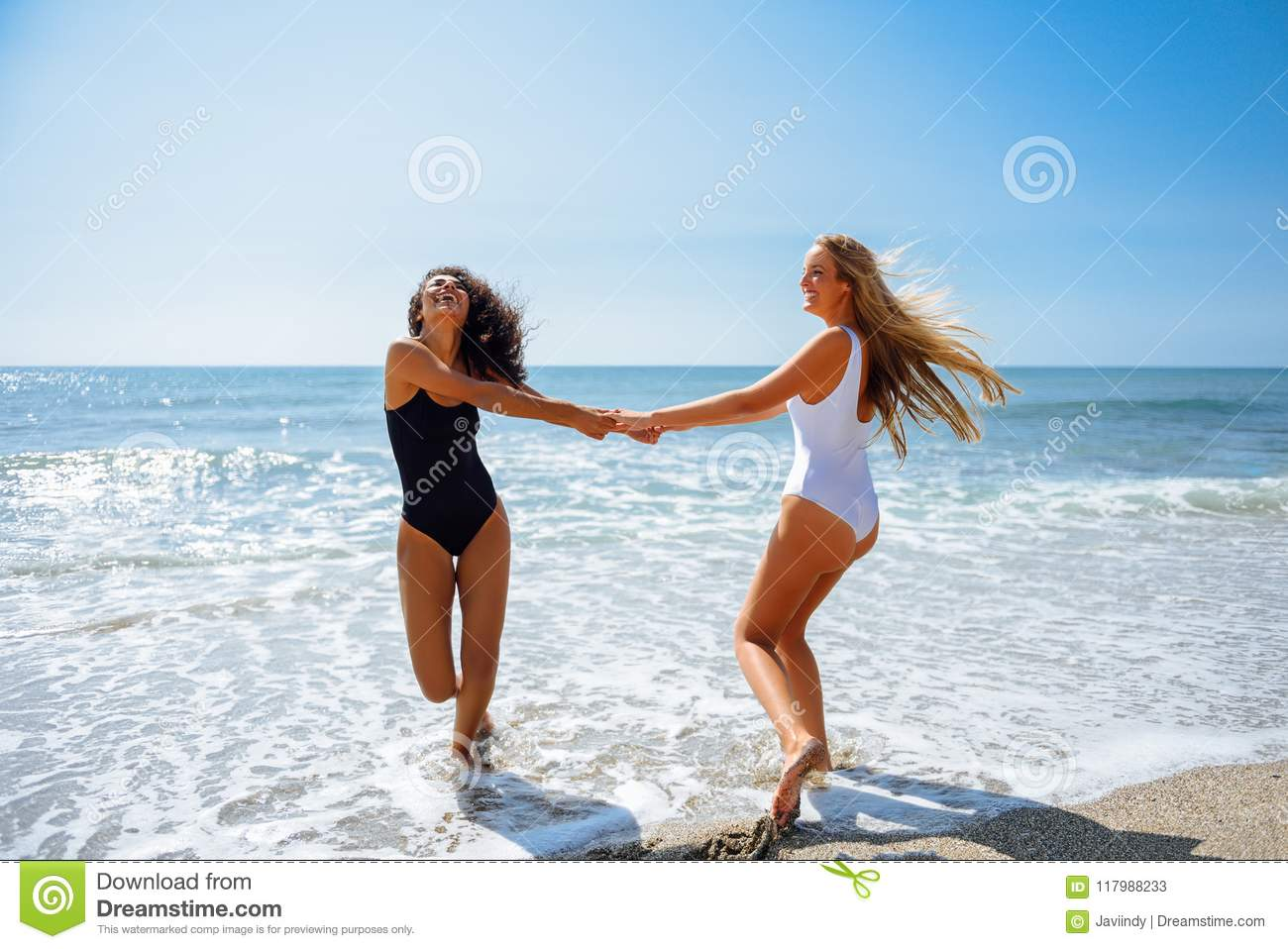851ac92dcba9a Two young women with beautiful bodies in swimwear having fun with their  hands caught on the beach. Funny caucasian and arabic females wearing black  and ...
