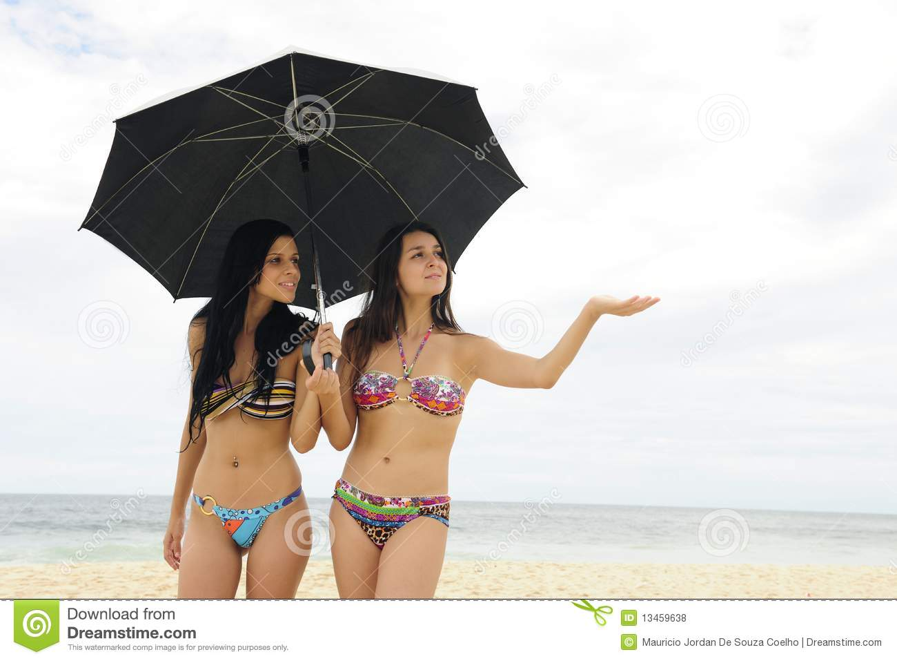 two women with umbrella on the beach royalty free stock