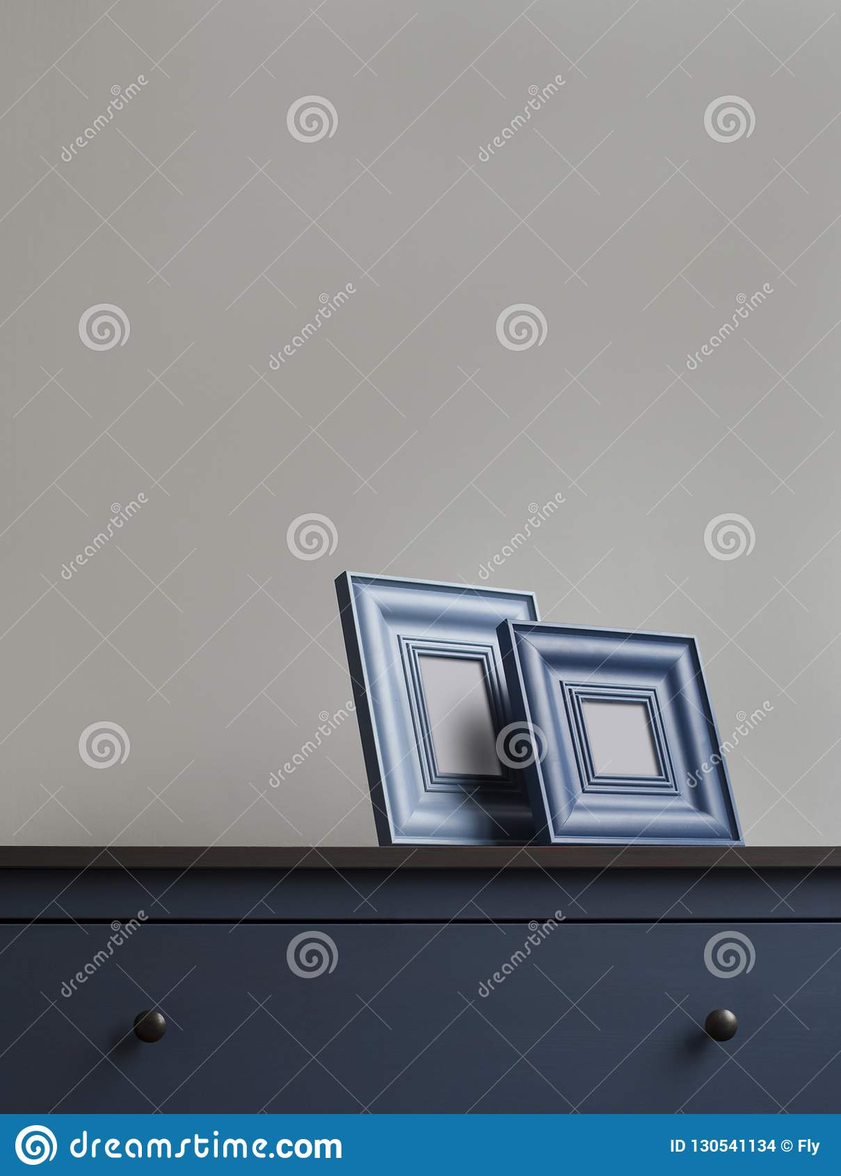 Two wooden picture frame on blue chest of drawers