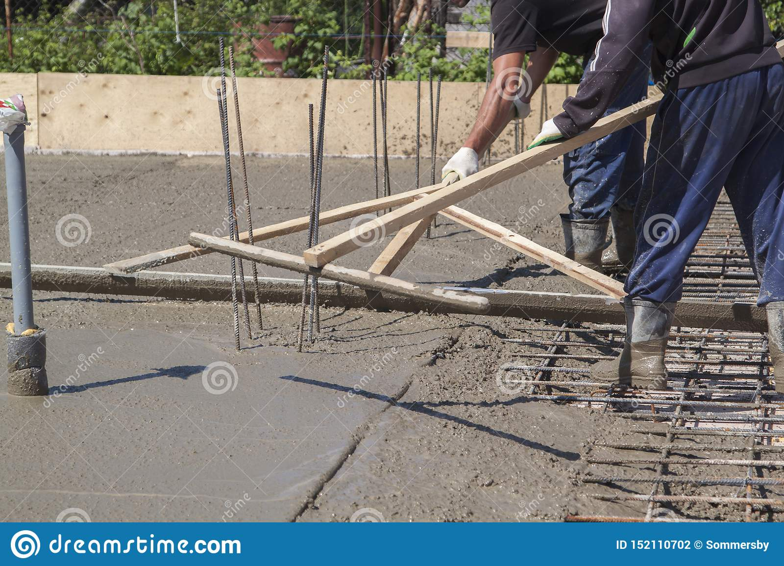 Two Workers Leveling Fresh Concrete Slab With A Special Wooden W Stock Photo Image Of Instrument Industry 152110702