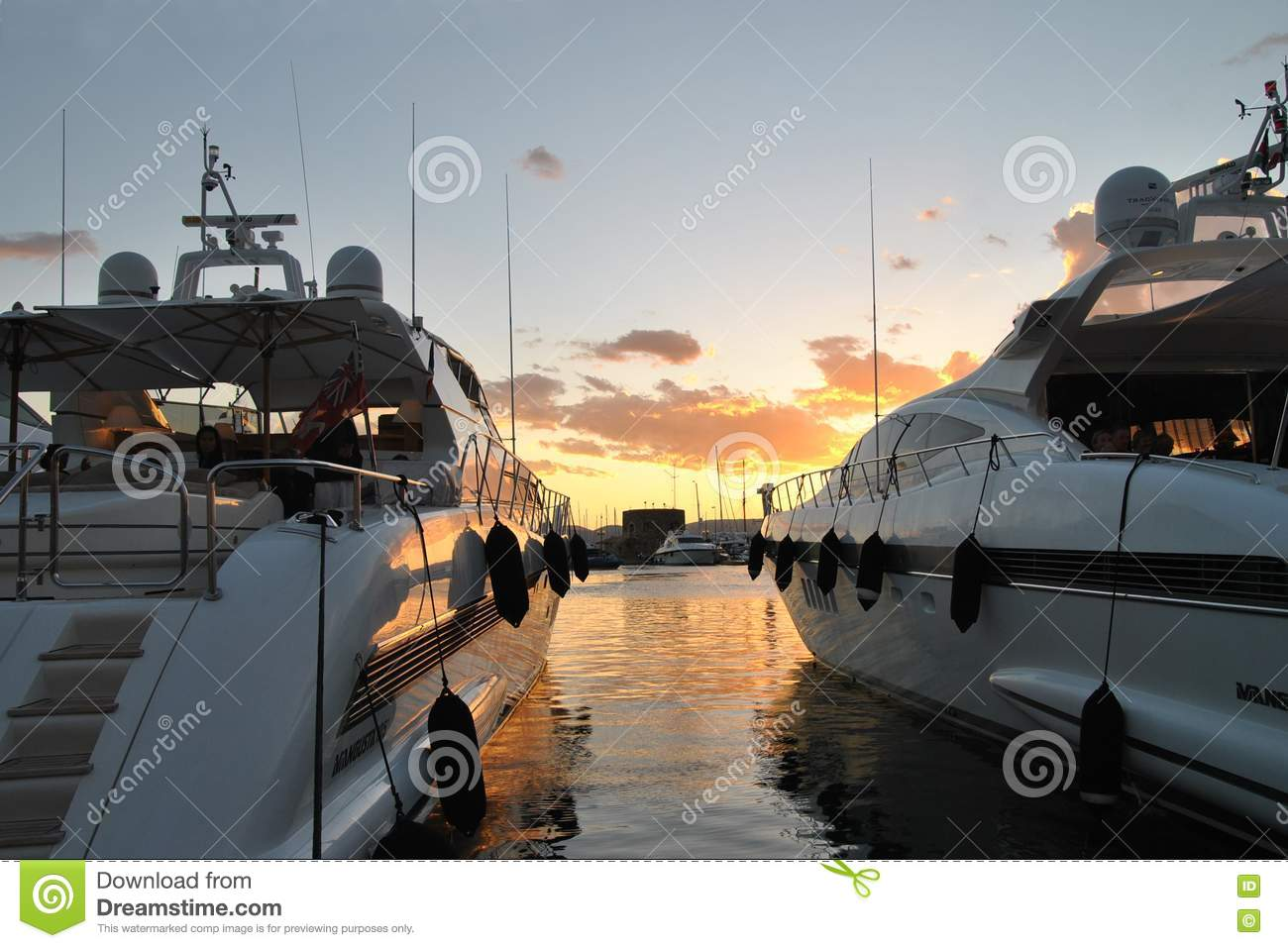 Two yachts on the sunset sky background